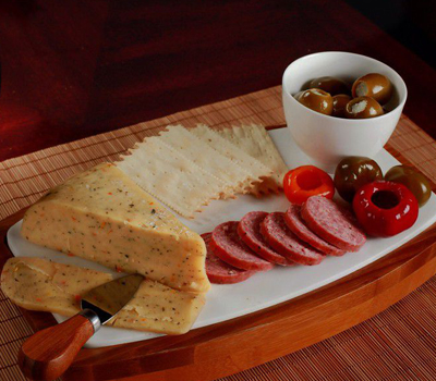 Plate of cheese, crackers, salami, peppers and olives.