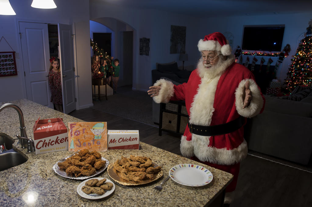 Santa surprised by plates of fried chicken on kitchen countertop
