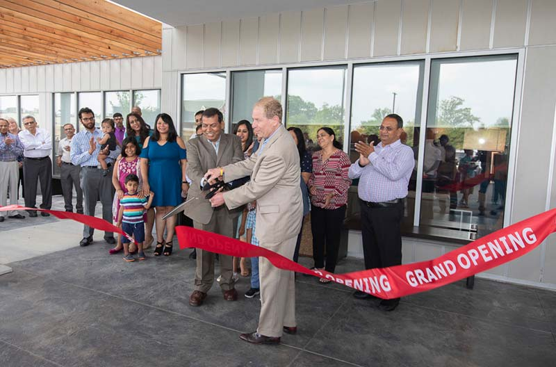 Cutting red ribbon at grand opening of a business