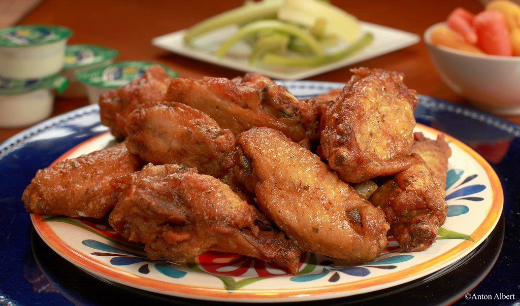 Closeup of a plate of chicken wings with celery, ranch and carrots in background