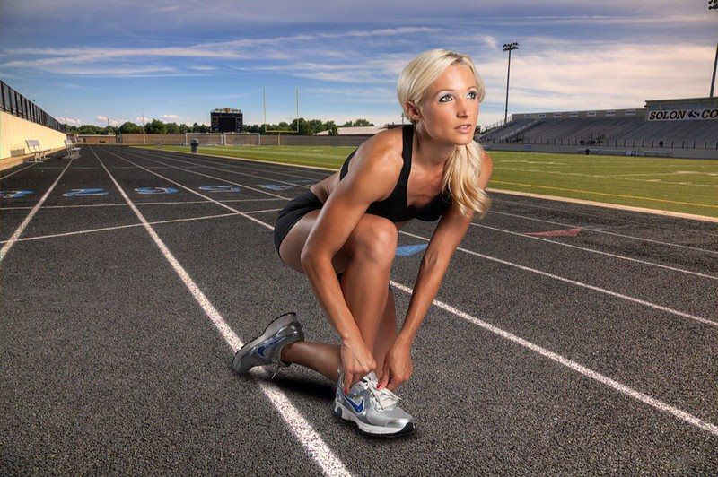 Female athlete tying her shoe on track